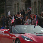 Vet Waves from Red Convertible