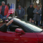 vets in red car with flags